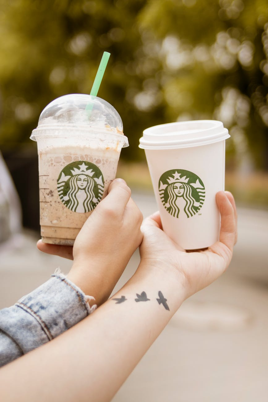 persons holding starbucks cups